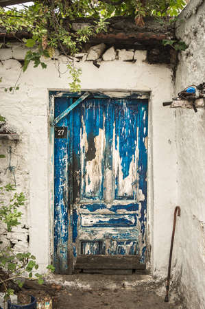 Blue scuffed timber door of the white house rural scenery photo