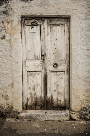 Old white timber door in the scuffed wall rural scenery photo