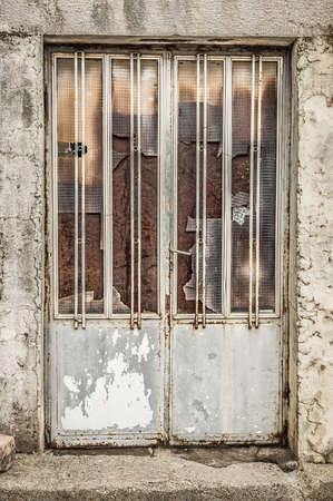 tatty: Old metallic door with broken glass in the scuffed wall