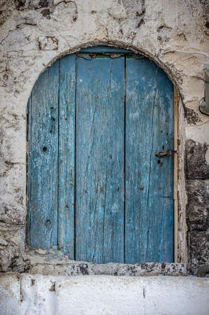 Old blue timber door in the scuffed wall rural scenery photo