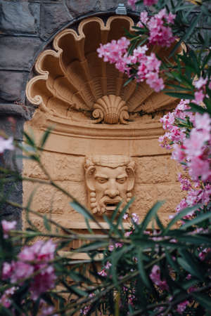 tragic: Architectural Detail of Fountain Tragic Mask in the frame of Oleander Flowers