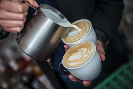 Barista making 2 cups of cappuccino at once pouring milk into coffee