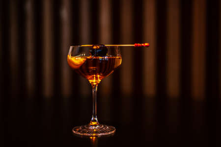 Coctail with Black Olive on the Stick on the Table