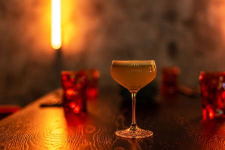 Beautiful cocktail with foam on the table in warm light reflections