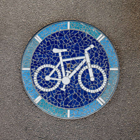 Mosaic in the Shape of Bike on the Hatch on a Bicycle Lane