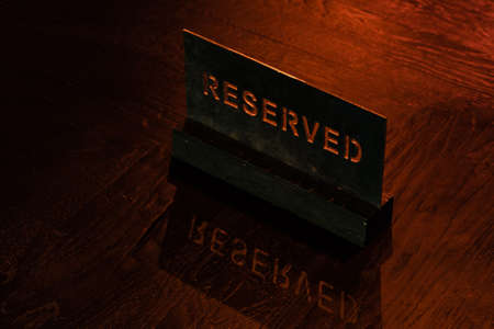 Reserved Stencil Wooden Table in the Restaurant with a Shadow Reflection 스톡 콘텐츠