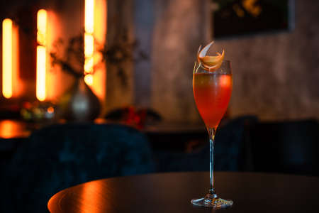 Cocktail in Layers with Orange Peel Decoration on the table in a restaurant 스톡 콘텐츠