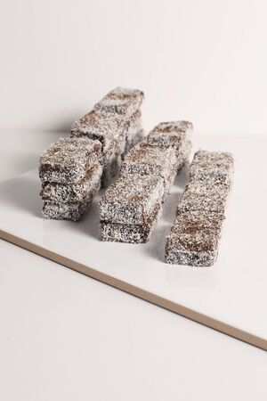 tucker: Group of Lamingtons on a white background.