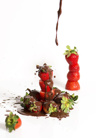 drizzle: A group of fresh strawberries and dark chocolate with a white background.