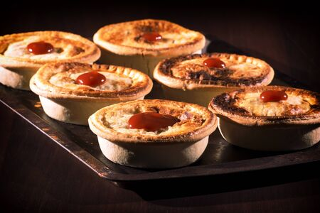 baked meat: Freshly baked meat pies with sauce and high contrast lighting.
