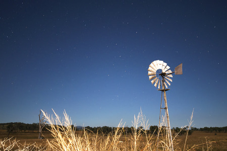 Windmill with stars in the background in the outback of Queensland Australia. High Noise.
