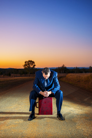 dirtroad: Concept: A frustrated business man is leaving the corporate lifestyle and chasing freedom in the outback of Queensland, Australia. Cinematic Portrait Style. Stock Photo