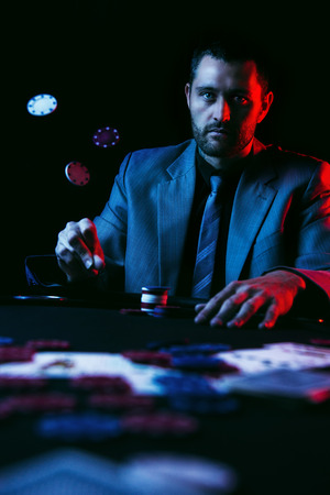 and the stakes: Concept: A high stakes poker player is frustrated and emotional over loosing and finding it hard to contain his emotions. Cinematic portrait.