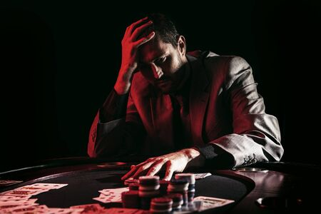 Concept: A high stakes poker player is frustrated and emotional over loosing and finding it hard to contain his emotions. Cinematic portrait.