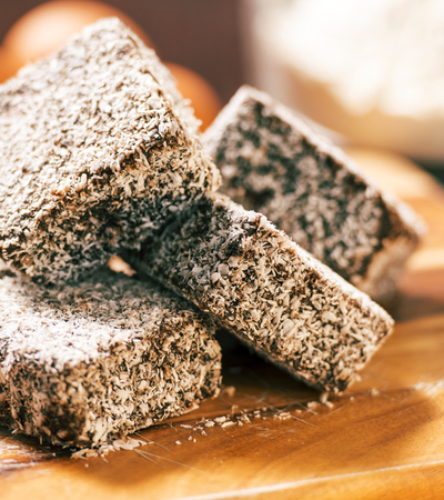 Group of Lamingtons on a timber cutting board with food ingredients in the background Banco de Imagens
