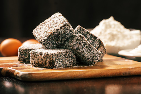 Group of Lamingtons on a timber cutting board with food ingredients in the background Stock Photo