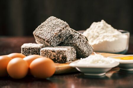 tucker: Group of Lamingtons on a timber cutting board with food ingredients in the background Stock Photo
