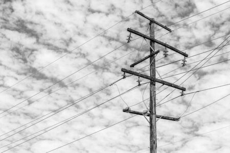 powerline: Aged timber power line pole with clouds and sky in the background during the day at Brisbane, Queensland Stock Photo