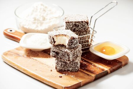 timber cutting: Group of Lamingtons on a timber cutting board with food ingredients in the background Stock Photo