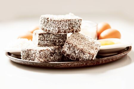 food tray: Group of Lamingtons on a timber metal baking tray with food ingredients in the background Stock Photo