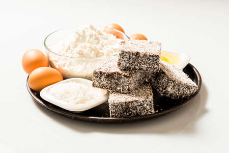 tucker: Group of Lamingtons on a timber metal baking tray with food ingredients in the background Stock Photo