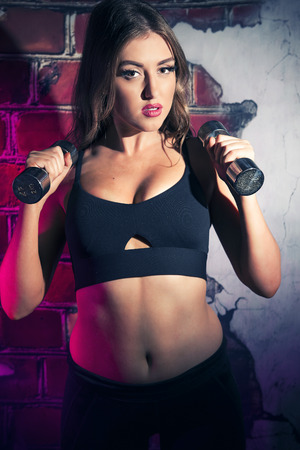 cinematic: Female fitness model posing in studio. Cinematic Portrait Style. Stock Photo