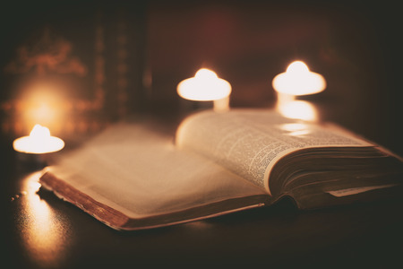 Bible with ghost pages turning and candles in the background