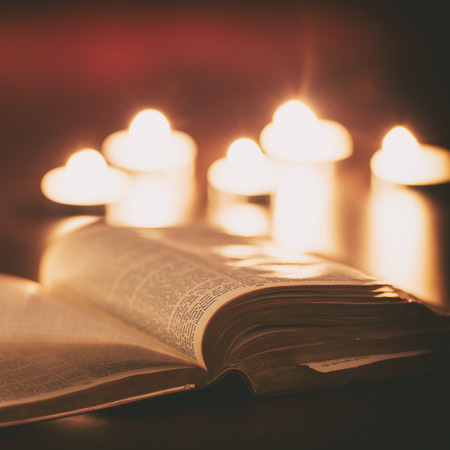 Bible with candles in the background. Low light scene. Stock Photo