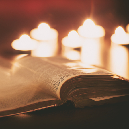 christian candle: Bible with candles in the background. Low light scene. Stock Photo