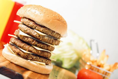food concept: Mega cheeseburger with potato chips and ingredients on a white background