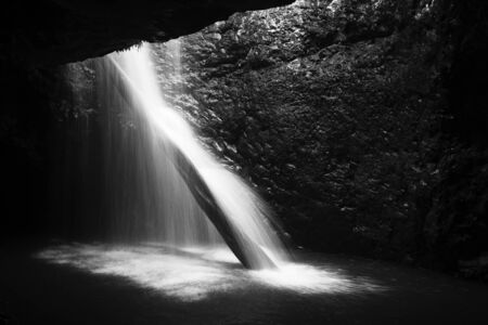 Natural Bridge Waterfall in Springbrook on the Gold Coast hinterlands, Queensland. Black and White image Stock Photo