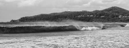 byron: Black and white image of Byron Bay beach and waves in New South Wales, Australia with Cape Byron lighthouse in the background. Stock Photo
