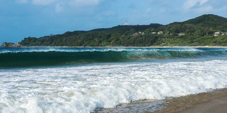 byron: Byron Bay beach and waves in New South Wales, Australia with Cape Byron lighthouse in the background.