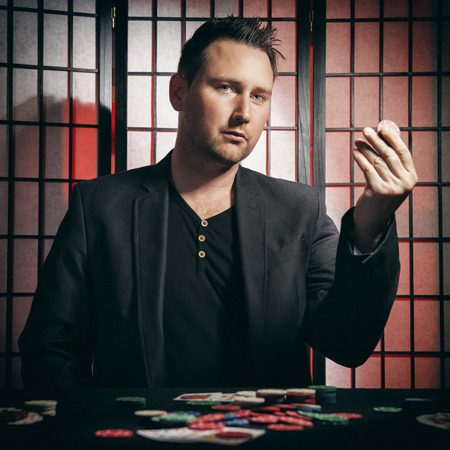 Concept: A high stakes poker player is winning big and feeling a little to confident against his opponents. He becomes overconfident and arrogant, showing of his chip stakes. Cinematic portrait. Stock Photo