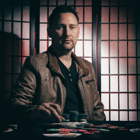 and the stakes: Concept: A high stakes poker player is winning big and feeling a little to confident against his opponents. He becomes overconfident and arrogant, showing of his chip stakes. Cinematic portrait. Stock Photo