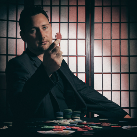 high stakes: Concept: A high stakes poker player is winning big and feeling a little to confident against his opponents. He becomes overconfident and arrogant, showing of his chip stakes. Cinematic portrait. Stock Photo