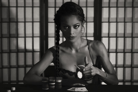 high stakes: Concept: A beautiful high stakes poker player is winning big and feeling sensual and confident. Cinematic portrait. Black and white image. Stock Photo
