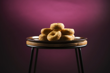 Fresh baked cinnamon donuts on a rustic metal baking tray.
