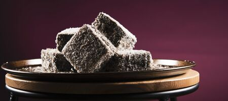 Group of Lamingtons on a metal baking tray.