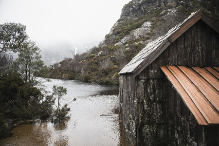 highlands region: Boat shed in Dove Lake, Tasmania on a snowy and overcast day. Stock Photo