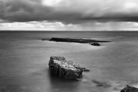 woody bay: Black and white. Long exposure of Woody Point beach and rocks. QLD, Australia. Stock Photo