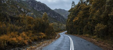 Road and mountains out in the Tasmanian country during winter on a rainy day. Stock Photo