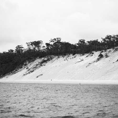 beachfront: View of the pristine beachfront at North Point, Moreton Island during the day. Black and White. Stock Photo