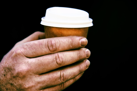 High contrast image of a small coffee cup in an older man's hand.