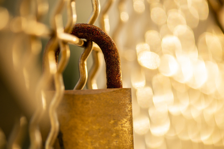 Closeup of a rusted padlock with golden bokeh Imagens