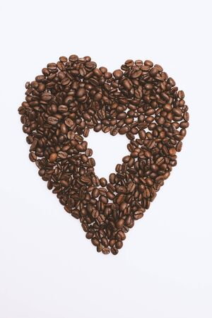 Scattered coffee beans on a white background.