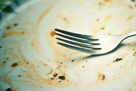 A dirty and empty dish with fork