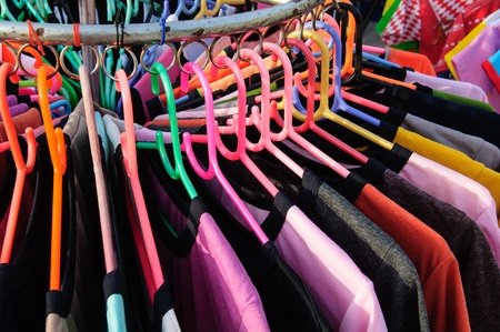 Colorful t-shirts on the hanger in the clothes shop photo