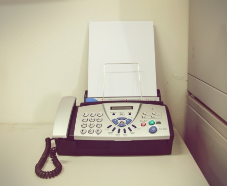 Telephone/ fax machine with handle on the hook.