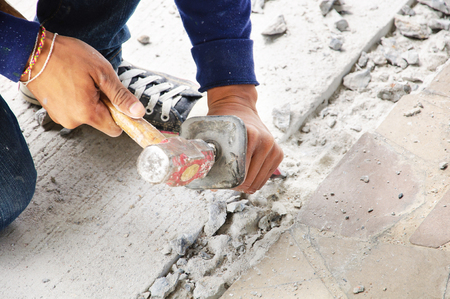 mason with chisel and hammer restores the concrete photo